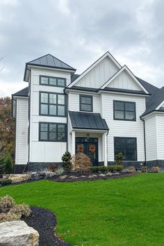 This white Modern Farmhouse-inspired home by Barrington Homes in Pittsburgh, Pa., features HardiePlank lap siding, HardiePanel siding, dark windows and trim, a stone water table, and metal roof accents. Click for more Modern Farmhouse design inspiration. Hardie Board Siding, Board And Batten Siding, Wood Siding, Modern Farmhouse Design, Farmhouse Ideas, Farmhouse Style, Barrington Homes, Vertical Siding, Dark Trim