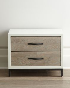 "Nightstand made of select hardwoods with elm and birch veneers. Gray and parchment finish; gunmetal finish on drawer pulls and base. Two drawers; flip top with power supply. 27""W x 18""D x 21""T. Import"