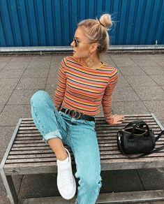 Dupla estilosa: Listras + jeans. Coque bagunçadinho, blusa de manga com listras coloridas, cinto de logo, calça mom jeans com barra dobrada, tênis branco