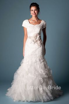 Mariska price $1475.00 - This modest wedding dress is a soft beaded lace gown, that has a sweetheart neckline with an organza and lace ruffle skirt. Matching lace covered buttons go down the entire...