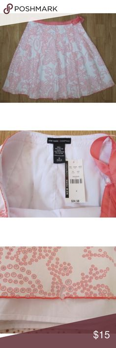 """NWT New York & Company Skirt eyelet lace full 4 So pretty!  New with tags New York & Company eyelet lace skirt in size 4.  White with a coral pink color.  There's a white layer underneath the top layer.  Side zip closure with attached ribbon tie.  I'm not sure whether this would be considered an A-line or full skirt.  **There is a tear between holes at the bottom of the skirt *see last photo.  Not very noticeable looking at it as a whole.  Measures about 23"""" long, and 31"""" around the waist…"""