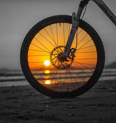 Sunset in a bicycle wheel - The use of  the bicycle is self-limiting. It allows people to create a new relationship between their life-space  and their life-time, between their territory and the pulse of their being, without destroying their  inherited balance. https://www.facebook.com/GreatMountainBiking/