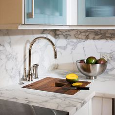 Choosing the same material for the countertops and backsplash creates a clean, uniform look that works especially well in contemporary kitchens. Here, classic marble serves as a stellar partner to modern white cabinets and stainless-steel hardware.