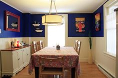 """Cobalt and cream dining room with vintage travel posters. Vermont, USA by Maren Mecham. Blue paint is Behr """"Sailboat Blue"""" and cream is """"Raffia Cream"""" from Home Depot."""