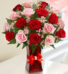 Shades of Pink and Red™ - Gorgeous bouquet of premium long-stem pink and red roses, accented by fresh waxflower and salal in a stylish red glass gathering vase $64.99- $89.99 #pinkandredroses #rosebouquets #roses