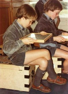 British preparatory school boys in sandals, sitting on their tuck boxes