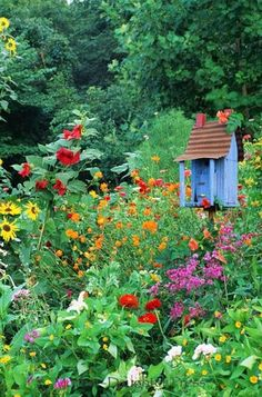 Blue Birdhouse with Tin Roof looks inviting in the perennial garden!