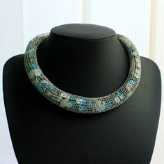 "Beautiful Grey Collar -Handmade Collar Necklace from "" Vlora Shileku"". This beautiful collar has a very unique design and it is made from blue, grey amd black sequins wrapped with silver coloured wire.  Material:This collar is made from wire and sequins."