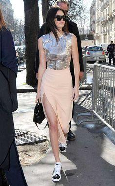 Kendall Jenner usa saia midi com fenda nude, top metalizado e tênis.