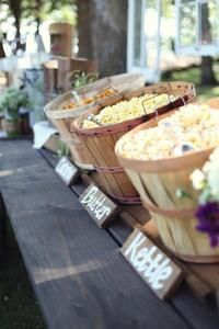 Popcorn set up at wedding reception with cute diy labels. Perfect for an outdoor summer or fall wedding. Snack material before a main course.