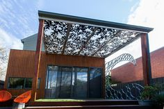 Paal Grant Landscaping featuring Galvanised Surf Bubble Wave and Banksia nut pergola roof panels for interesting shadowing
