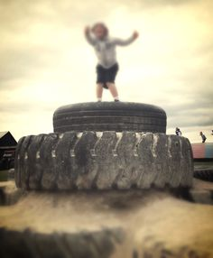I'm king of the world! Or at least this mountain of tires! Field trip fun at the Pumpkin Patch! #ThanksPinning