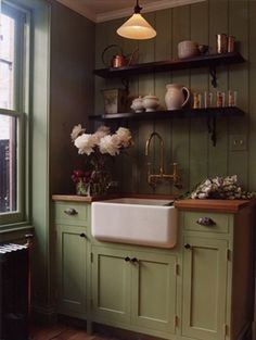 .Painted wood cabinets, farmhouse sink, wall-mounted faucet