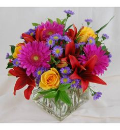 Large Cubed Vase filled with very colorful flowers. Lilies, Gerberas, Roses Aster and assorted greenery.
