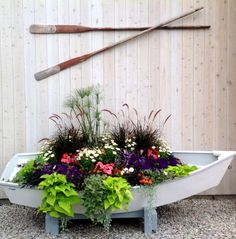 Awesome Porch and garden planters with a coastal theme. Boat planter... and more.