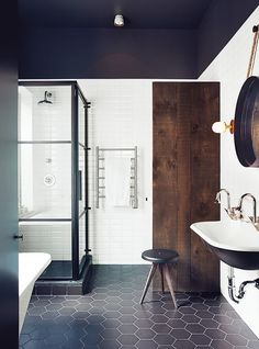 Minimalist bathroom with black ceilings, honeycomb black floor tile and wooden accents