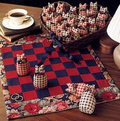 """Cat Checkerboard Game Sewing ePattern - Playing checkers will be purr-fectly fun with this patchwork checkerboard mat and stuffed cat game pieces. The mat is easy to strip-piece with contrasting fabrics and a pretty border print. The sitting kitties are sewn using two different prints. Metal washers are placed on the kitties when they are kinged. Number of Designs: 1 checkerboard mat with stuffed cat game pieces Approximate Design Size: Checkerboard 18"""" x 22""""; each cat 4"""" tall"""