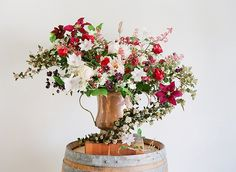 A large reclaimed copper vessel contains peonies, clematises, physocarpus, lacecap hydrangeas, coral bells, and columbine.