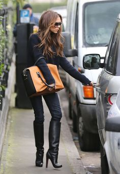 Victoria Beckham with her Spring 2012 orange-and-black suede tote