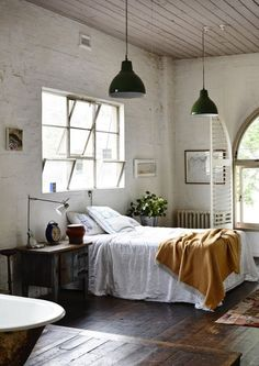 Industrial chic modern loft living space.  Bedroom with hanging pendant lighting.