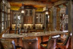 Home bar in a log home with leather chairs and stone bat top