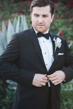 Groom looking quite handsome in his tux and rose boutonniere. Wedding Photographer: Randy + Ashley.