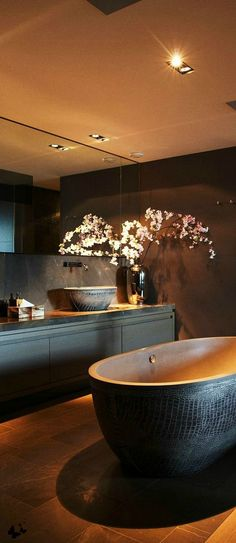 Black freestanding tub in luxurious black and gold bathroom