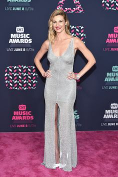 Erin Andrews in a low-cut, high-slit silver Maria Lucia Hohan gown featuring a sheer skirt, white pumps, with Nigaam and Tacori bracelets