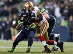 Running back Marshawn Lynch #24 of the Seattle Seahawks carries the ball as defensive end Ray McDonald #91 of the San Francisco 49ers defends during the 2014 NFC Championship at CenturyLink Field on January 19, 2014 in Seattle, Washington.