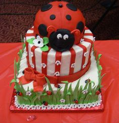 This is a ladybug themed baby shower cake. Three tiers, bottom two buttercream and top is all fondant. Grass is a 50/50 fondant/gumpaste mix. Ladybugs were individually made out of fondant and painted by hand. Bow is gumpaste and flowers are fondant