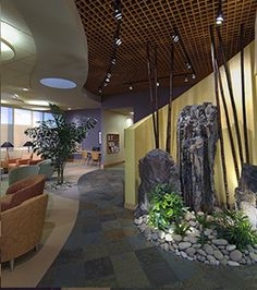 Granite boulders have water cascading over them and bamboo that continues up through the wood celing grid. Discs of white fabric diffuse the lighting. A children's play area lies beyond the curved wall.