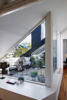 petit toit-terrasse moderne et vitré aménagé avec un canapé décoré de coussins, un tapis extérieur et des plantes vertes en pots