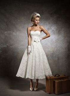 Justin Alexander wedding dresses style 8632 Strapless alencon sweetheart, silk dupion pleated cummerbund accented with silk flower and feather, circular cut lace tea length skirt. Buttons over back zipper.