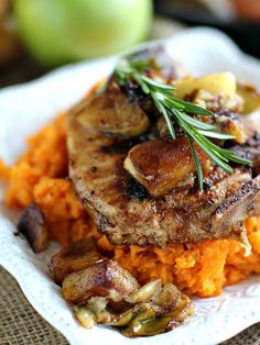 Apple Cinnamon Pork Chops with fresh rosemary, brown sugar and cinnamon apples served on a bed of fluffy, mashed sweet potatoes.