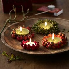Tea Lights with berries glued to the metallic covering & placed in a wooden bowl.