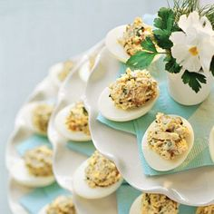 Lemon-Dill Chicken Salad-Stuffed Eggs | Give this Southern favorite fresh flavor by adding dill and shredded chicken. Stacked white cake stands decorated with colored paper napkins create a snappy yet casual centerpiece. | SouthernLiving.com