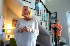 Scituate 07/09/2018: Lisa Blake, a professional organizer, stands next to her Command Central space in the corner of the staircase of her Scituate home. The space was created to organize and post her three boys schedules for upcoming events. (l-r) Wyatt Maldonis, 8, and his twin Hunter, 8, walk down the staircase as their older brother Mason, 9, looks on. Photo by Debee Tlumacki for the Boston Globe (regional)