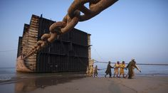 The Ship Breakers - In Focus - The Atlantic Laborers pull an iron rope before separating a portion of a ship into scrap metal at Gaddani ship breaking yard, on November 25, 2011. (Reuters/Akhtar Soomro)