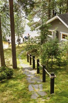 Rantaan laskeutuvat liuskekiviportaat. Kaunis kaide tehtiin sopivan mittaisiksi sahatuista vanhoista puhelinpylväistä. Ne käsiteltiin tervansävyisellä puuöljyllä ja niihin porattiin köyden paksuiset reiät. Ensin riittävän pitkää köyttä ei meinannut löytyä. Lopulta onnisti, kun Kuopion Hongkongissa myytiin paksua kymmenmetristä köyttä sopuhintaan. Lake Cottage, Cottage Homes, Garden Cottage, Cottage Design, Cottage Style, Summer Cabins, Hummingbird Garden, Outdoor Retreat, Cabins And Cottages
