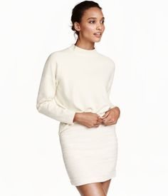 Natural white. Short skirt in textured-weave, cotton-blend fabric. Concealed button and zip at side. Polyester content is recycled.