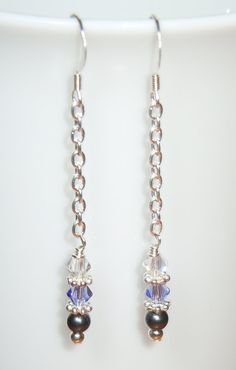 Earrings made of Swarovski 4mm crystal bicones in tanzanite purple and crystal with black pearls and a sterling silver ball on silver chain.