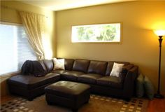 yellow living room walls | Large Living Room With Black Leather Sofa Bed And Yellow Wall Paint ...