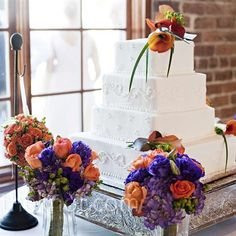 Alternating layers of Swiss dots and elegant scroll patterns gave the couple's all-white cake visual texture. A cluster of flame calla lilies on the top tier gave the confection a burst of color.