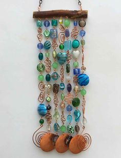 This glass beaded wind chime and sun catcher is the perfect way to brighten your patio, yard, a kitchen window or even a wall! I used mesquite wood and copper wire to string the glass beads. I included some copper wire that I shaped into curly whirlies and hammered to add extra dazzle. The strands are finished with hammered copper discs and shaped copper wire that make a subtle but pleasant sound. My intention is to show a luminous glow and glistening of color in the sun light and even the…
