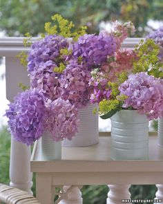 Reuse tin cans, spray painting them white and using them for vases to hold flowers outdoors.