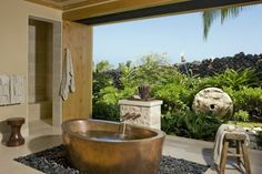 master bath opens to a lush tropical garden....coper soaking tub is the central visual feature and also a great place to relax and enjoy the sweet hawaiian breeze