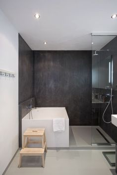 Les murs en béton de cette salle de bains apporte l'aspect moderne. La douche ainsi que la baignoire sont positionnées dans le même espace. Nous aimons beaucoup le tabouret en bois. [vu sur archdaily.com]