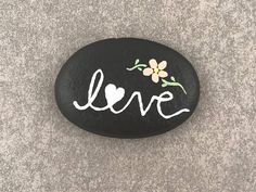 This Love - Kindness Stone is hand painted, made with a smooth, natural rock found on the shore of a Rhode Island beach. This uplifting rock makes a great home decoration or gift. This rock is painted with gloss acrylic paint, sealed for indoor or outdoor use. It measures approximately .25 height, 1.5 width, 2 length. This listing includes: (1) Love Painted Rock If youd like to order more than the available quantity or for any custom orders feel free to contact me and Id be happy to help…