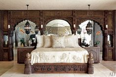In the master suite of Cher's Indian-Inspired Los Angeles Duplex, Lawrence-Bullard designed the bed using antique Indian panels. He made the bedside tables with antique inlaid doors. An Indian palace façade conceals Cher's dressing room. Distressed mirrors reflect bronze lanterns from Marrakech. The floors are antiqued limestone.