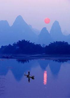 A Cormorant Fisherman at sunset on the Li River near Xing Ping. Guangxi Province – Southern China.